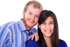 在蓝色的愉快的年轻人种间夫妇,笑 库存照片