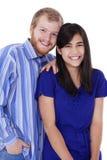 在蓝色的愉快的年轻人种间夫妇 免版税库存图片
