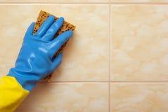 在蓝色的手与黄色手套 库存照片