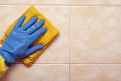 在蓝色的手与黄色手套 免版税库存照片