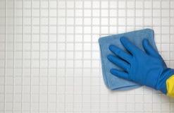 在蓝色的手与黄色手套 图库摄影