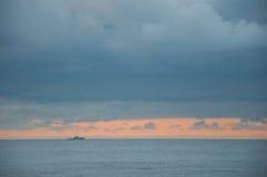 在蓝色的海景与在天际的一艘船 免版税库存照片
