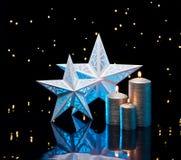 在蓝色的由后面照的星与银色蜡烛 免版税库存图片