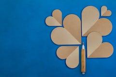 在蓝色皮革背景的纸心脏与木铅笔 免版税库存照片