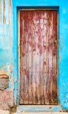 在蓝色砖墙上的退色的红色门有残破的膏药的 库存图片
