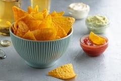 在蓝色碗的嘎吱咬嚼的烤干酪辣味玉米片在桌上用垂度调味汁和啤酒 库存照片