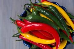 在蓝色碗的红色,绿色和黄色墨西哥辣椒冠上 库存图片