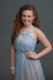 在蓝色礼服陈列微笑表示的青少年的秀丽 免版税库存照片