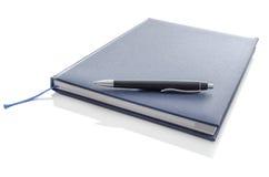 在蓝色笔记本的笔 免版税库存图片