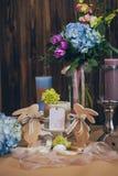 在蓝色紫罗兰色口气的惊人的婚礼花束与事件的蜡烛美丽的土气木葡萄酒装饰 库存图片