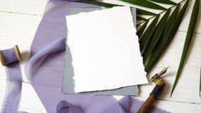 在蓝色织品背景的白色空白的贺卡丝带与棕榈叶和书法笔的在白色 股票视频