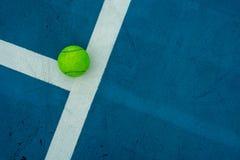 在蓝色网球场的唯一网球 免版税库存图片