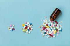 在蓝色背景、增长的疗程用途和恶习的五颜六色的药物药片在世界概念的 免版税库存照片