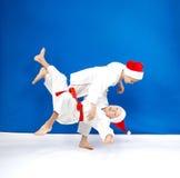 在蓝色背景两运动员训练柔道摔 免版税库存图片