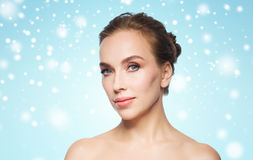 在蓝色背景和雪的美丽的妇女面孔 库存图片
