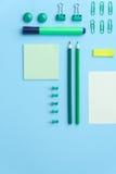 在蓝色背景桌上的办公用品 库存图片