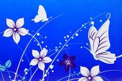 在蓝色背景画的白花和蝴蝶 免版税库存照片