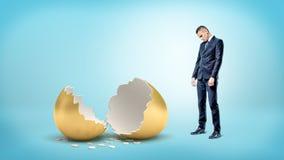 在蓝色背景的一个哀伤的商人在一个大打破的金黄鸡蛋看下来 免版税图库摄影