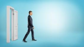 在蓝色背景的一个商人走通过一个开放白色门框的 图库摄影