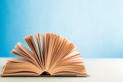 在蓝色背景的一本开放精装书 免版税库存照片