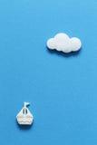 在蓝色背景的一条小船 图库摄影