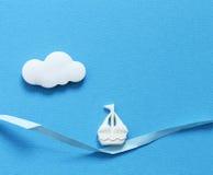 在蓝色背景的一条小船 库存照片