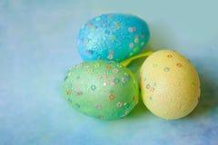 在蓝色背景的三个五颜六色的手工制造复活节彩蛋 免版税库存照片
