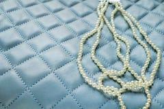 在蓝色背景的三颗子线珍珠 图库摄影