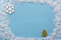 在蓝色背景的人为雪框架与雪花和冷杉 库存照片