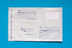 在蓝色背景的俄国岗位聚乙烯信封 塑料邮政邮寄的袋子 免版税库存照片