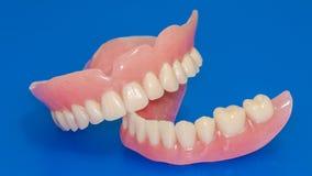 在蓝色背景的假牙 库存图片