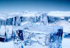 在蓝色背景的冰块 图库摄影