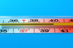 在蓝色背景的医疗水银温度表 免版税库存图片