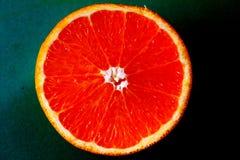 在蓝色背景的半有机红色桔子 免版税库存照片