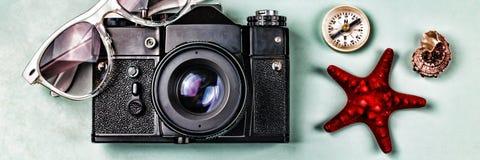 在蓝色背景的古老照相机、指南针和海纪念品 免版税库存照片