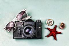 在蓝色背景的古老照相机、指南针和海纪念品 免版税库存图片