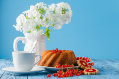 在蓝色背景的可口柠檬蛋糕用莓果和花 库存图片