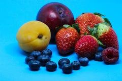 在蓝色背景的各种各样的果子 免版税库存图片