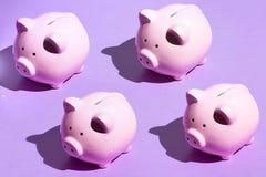 在蓝色背景的四陶瓷moneyboxes 库存图片