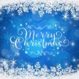在蓝色背景的圣诞快乐在一个多雪的框架 库存照片