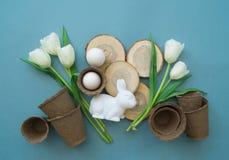 在蓝色背景的复活节装饰构成 白色兔子、郁金香、花盆、没有漆的鸡蛋和树 免版税库存照片