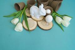 在蓝色背景的复活节装饰构成 白色兔子、郁金香、花盆、没有漆的鸡蛋和树 免版税库存图片