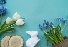 在蓝色背景的复活节装饰构成 白色郁金香、花盆、没有漆的鸡蛋和树 免版税库存图片