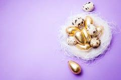 在蓝色背景的复活节金黄鸡蛋 免版税库存照片