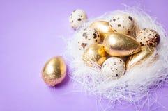 在蓝色背景的复活节金黄鸡蛋 免版税图库摄影