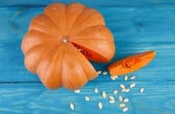 在蓝色背景的大鲜美南瓜 在倾吐的餐馆沙拉的主厨概念食物新鲜的厨房油橄榄 免版税图库摄影