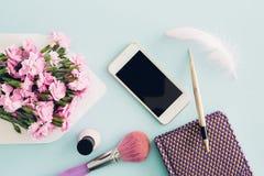在蓝色背景的女性平的位置,妇女有信封的` s桌面顶视图,花、笔、笔记薄和smartpho 免版税库存图片