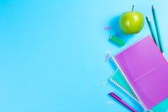 在蓝色背景的学校文具与copyspace 免版税库存照片