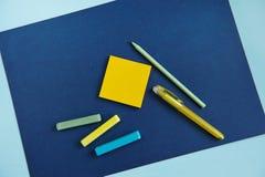 在蓝色背景的学校用品,顶视图 库存照片
