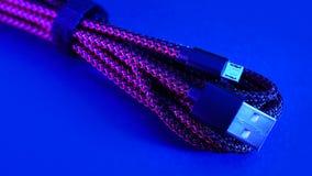 在蓝色背景的微USB缆绳 库存照片